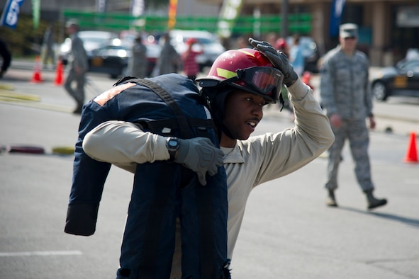 U.S. Air Force Staff Sgt. Mathew Berry, 51st Aerospace Medicine Squadron flight and operation medical technician, carries a dummy during Fire Muster 2016 on Osan Air Base, Republic of Korea, Oct. 13, 2016.  Osan's firefighters organized the fire muster to bring awareness to Osan for Fire Prevention Week Oct. 9-15.  The fire muster put together teams of four in a relay race with teams competing in a variety of firefighting skills. (U.S. Air Force photo by Staff Sgt. Jonathan Steffen)