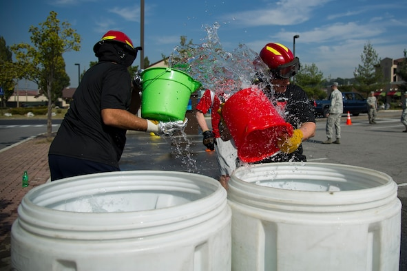 A team from 51st Civil Engineer Squadron emergency management grabs buckets of water for a relay race during Fire Muster 2016 on Osan Air Base, Republic of Korea, Oct. 13, 2016.  Osan's firefighters organized the fire muster to bring awareness to Osan for Fire Prevention Week Oct. 9-15. The fire muster had six stations for the four-person team run-through. (U.S. Air Force photo by Staff Sgt. Jonathan Steffen)