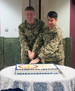 """161013-N-YB753-049 NAVAL SUPPORT ACTIVITY BAHRAIN (Oct. 13, 2016) Petty Officer 3rd Class Michael Joy, left, cuts the Navy birthday cake with Vice Adm. Kevin Donegan, Commander U.S. Naval Forces Central Command, during a ceremony honoring the Navy's 241st birthday at Naval Support Activity Bahrain. In keeping with naval tradition, the youngest and oldest Sailors present have the first pieces of cake. Sailors worldwide observed the Navy birthday on Oct. 13 with this year's theme of """"America's Sailor: For 241 years, Tough, Bold and Ready."""""""
