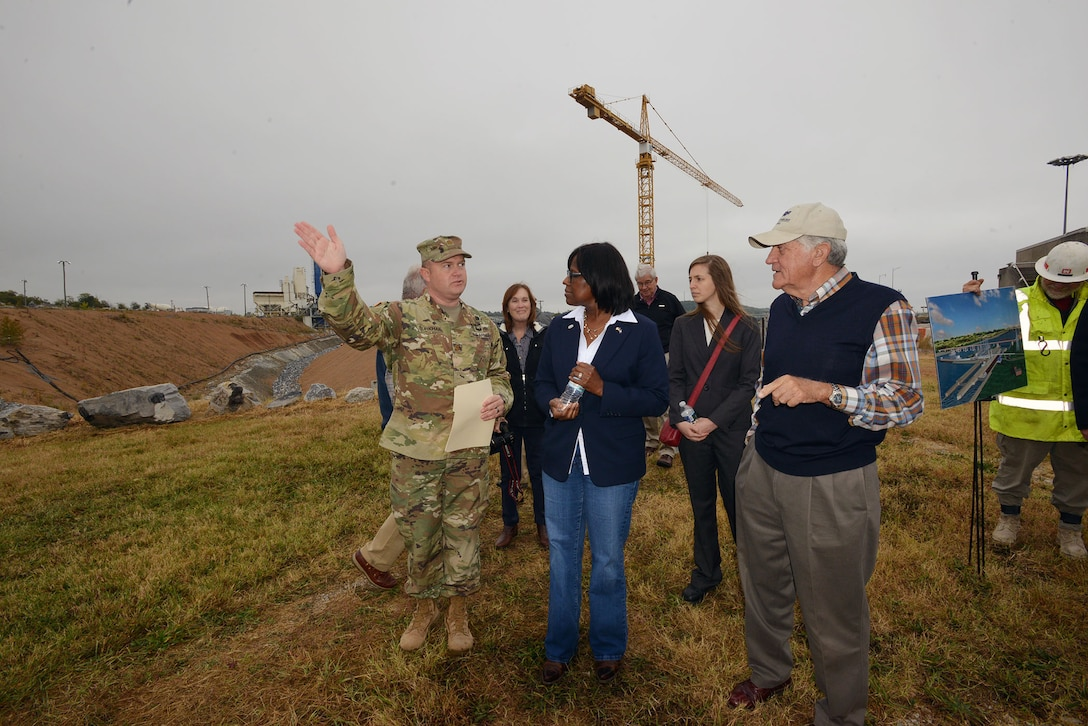 Maj. Christopher W. Burkhart, U.S. Army Corps of Engineer, Nashville District deputy district engineer provides a brief to  Kentucky Lt. Gov. Jenean Hampton, and 12 Tennessee Tombigbee Waterway Development Authority board members during a tour of the Kentucky Lock Addition Project  Oct. 13, 2016.
