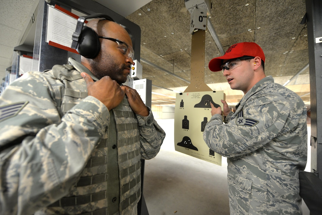 (from left) U.S. Air Force Staff Sergeant Brison King, 88th Medical Group medical logistic journeyman, receives instruction from Senior Airman Sterling Benson, 88th Security Forces Squadron combat arms instructor, during his pre-deployment weapons training at the SFS gun range, at Wright-Patterson Air Force Base, Ohio, Sept. 13, 2016. All U.S Air Force personnel are required to qualify on a weapon when deploying worldwide. (U.S. Air Force photo/Al Bright)