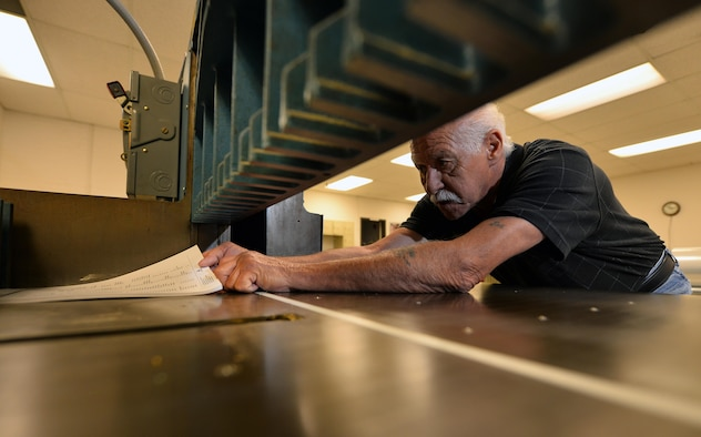 Joe Knott, an electronic duplicating systems technician with Defense Logistic Agencies Document Services, prepares to cut a ream of paper with a Challenger 370C cutter inside of the document services print shop located in the Martin Bomber Building on Oct. 6, Offutt Air Force Base, Neb.  Joe has been working within the print shop since he was hired in 1979.