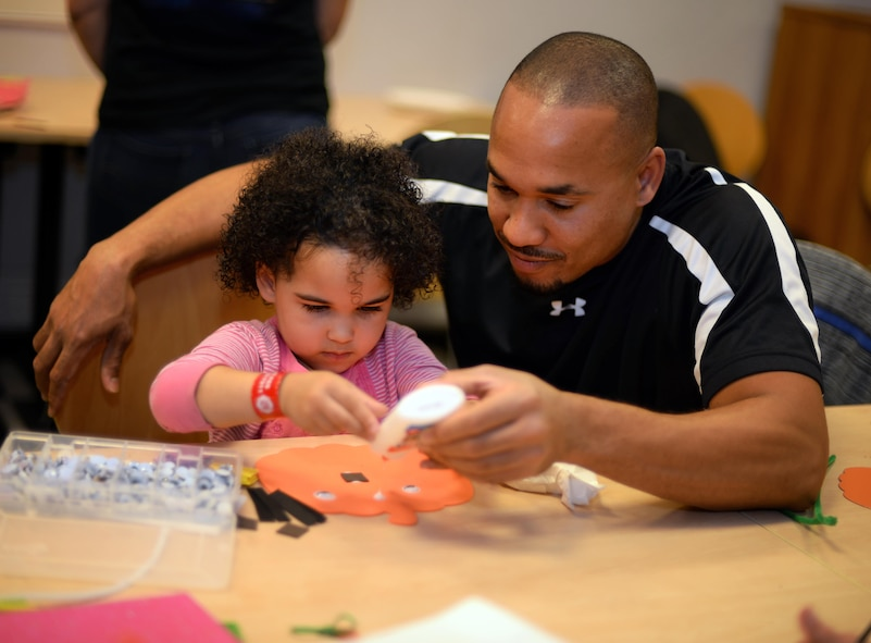 Kareem McKenzie, spouse of U.S. Air Force Master Sgt. Kelly McKenzie, 48th Fighter Wing Continuous Process Improvement office superintendent, creates a pumpkin with his daughter Oct. 14, 2016, on RAF Mildenhall, England. The Exceptional Family Member Program hosted a bowling night for all of its members, where they could create crafts and bowl for free. (U.S. Air Force photo by Senior Airman Christine Halan)