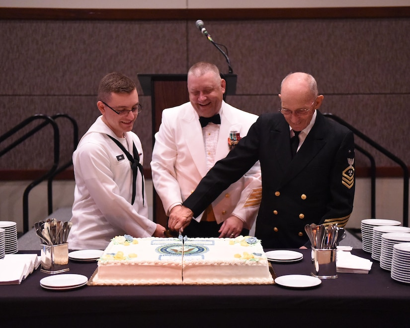 Seaman Charles Diehl (left), Navy Nuclear Power Training Command machinist mate, Master Chief Petty Officer Asa Worcester (center), Joint Base Charleston command master chief and Sam Kirton, a retired Navy Master Chief Petty Officer, cut the cake during the Navy Ball celebrating the Navy's 241st birthday. The event took place at the Embassy Suites Hotel, Charleston, South Carolina on Oct. 15. Navy tradition is to have the cake cut by the youngest and oldest Navy members present.