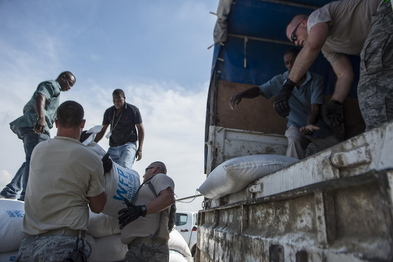 Airmen from the 621st Contingency Response Wing help unload rice from a World Food Program truck Oct. 9, 2016, in Port-Au-Prince, Haiti. The Airmen were working alongside Haitian citizens to provide relief after the nation was struck by Hurricane Matthew. (U.S. Air Force photo/Tech. Sgt. Russ Scalf)
