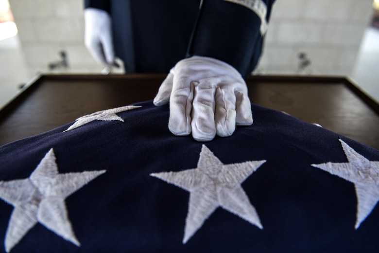 A member of the Moody Air Force Base Honor Guard places a hand on a folded United States flag before a funeral, Oct. 13, 2016, in Jacksonville, Fla. Moody's honor guard performs congressionally mandated honors throughout 51 counties within Southern Georgia and Northern Florida. (U.S. Air Force photo by Airman 1st Class Janiqua P. Robinson)