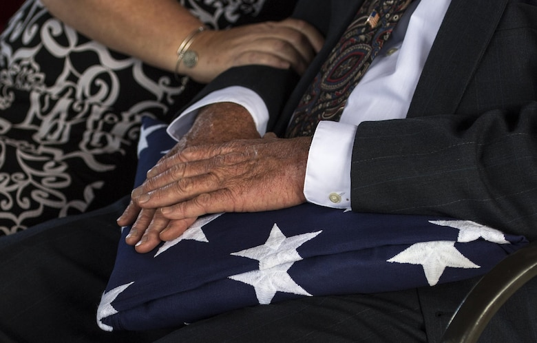 A family member of a fallen military member holds a United States flag during a funeral, Oct. 13, 2016, in Jacksonville, Fla. Once the honor guard has completed all ceremonial honors, the flag is given as a memorial to a family member. (U.S. Air Force photo by Airman 1st Class Janiqua P. Robinson)