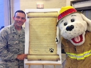 U.S. Air Force Col. David Benson, 7th Bomb Wing commander, and Sparky the Fire Dog, sign the Commander's Proclamation for fire safety and prevention at Dyess Air Force Base, Texas, Oct. 6, 2016. The Commander's Proclamation outlined Dyess' commitment to fire prevention and safety. (Courtesy photo)