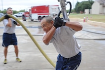 U.S. Air Force Master Sgt. Galli Delfin, 7th Civil Engineer Squadron operations engineering superintendent, carries a hose as part of the Fire Muster at Dyess Air Force Base, Texas, Oct. 14, 2016. The Fire Muster, as part of Fire Prevention Week, was designed to give participating Airmen an opportunity to see what firefighters have to do, from donning the gear to using a high-pressured hose, when responding to an emergency. (U.S. Air Force photo by Airman 1st Class Rebecca Van Syoc)
