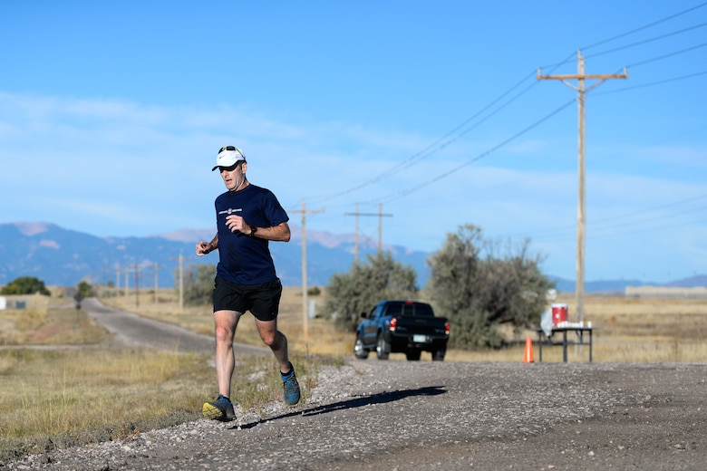 Mike Wasson runs past a water station during the 11th annual Schriever Air Force Base Half Marathon at Schriever Air Force Base, Colorado, Friday, Oct. 14, 2016. Wasson took first place overall with a time of 1:30:59, nearly 10 minutes in front of the second-place finisher. (U.S. Air Force photo/Christopher DeWitt)