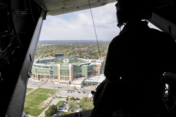 Staff Sgt. Dustin Trevino, a flight engineer with the 8th Special Operations Squadron, looks at Lambeau Field from a CV-22 Osprey tiltrotor aircraft over Green Bay, Wis., Oct. 14, 2016. The 8th SOS visited the Milwaukee-Green Bay area for a flyover above Lambeau Field Oct. 16 during the Green Bay versus Dallas NFL game. The Osprey offers increased speed and range over other rotary-wing aircraft, enabling Air Force Special Operations Command aircrews to execute long-range special operations missions. (U.S. Air Force photo by Airman 1st Class Joseph Pick)
