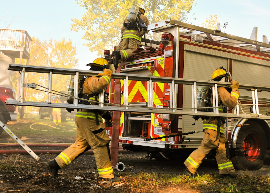 Airmen of the 174th Attack Wing Fire Department ready a ladder for access to the roof of a simulated burning building during an exercise held on Hancock Field Air National Guard Base Oct. 15, 2016. The exercise was part of a unit effectiveness inspection capstone. (U.S. Air National Guard photo by Staff Sgt. Duane Morgan)