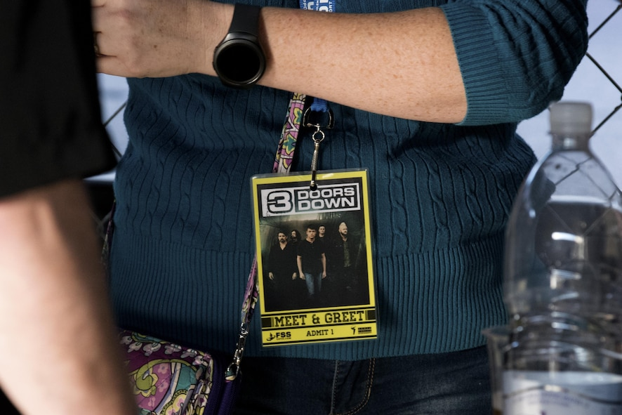 """A woman wears a """"meet and greet"""" pass around her neck before a 3 Doors Down rock concert inside Hangar 1 at Spangdahlem Air Base, Germany, Oct. 16, 2016. Some Sabers qualified for credentials to meet and have pictures taken with members from the group. The American rock band was a part of the Armed Forces Entertainment tour, an Air Force command operation, which brings entertainment to U.S. military personnel serving overseas. (U.S. Air Force photo by Airman 1st Class Preston Cherry)"""