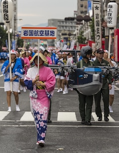 U.S. Marines and Sailors from Marine Corps Air Station Iwakuni march with members of Japan Maritime Self-Defense Force Fleet Air Wing 31 and Japanese civilians during the 60th Annual Iwakuni Festival in Iwakuni City, Japan, Oct. 16, 2016. The goal of the festival is to enrich the Iwakuni image, show the development of the community and build relationships between Iwakuni civilians. (U.S. Marine Corps photo by Lance Cpl. Aaron Henson)