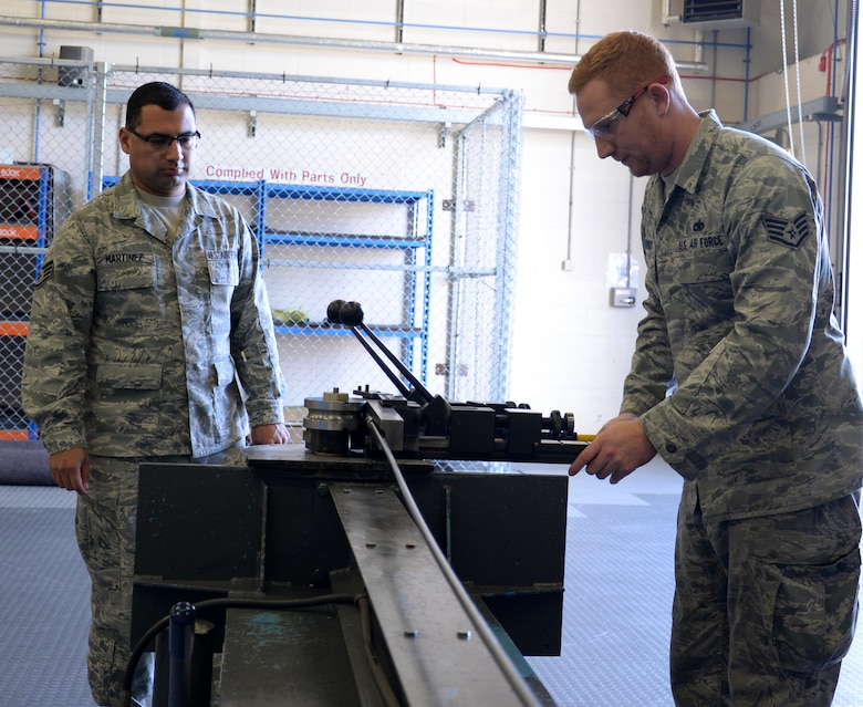 U.S. Air Force Staff Sgt. Jose Martinez, left, 100th Air Refueling Wing NCO in charge of inspections and analysis, ensures U.S. Air Force Staff Sgt. Zachary Sidlovsky, 100th Maintenance Squadron Aircraft Structural Maintenance craftsman, uses equipment safely Oct. 17, 2016, on RAF Mildenhall, England. Martinez and the rest of the safety office periodically go into shops to ensure Airmen are following safe procedures. (U.S. Air Force photo by Gina Randall)