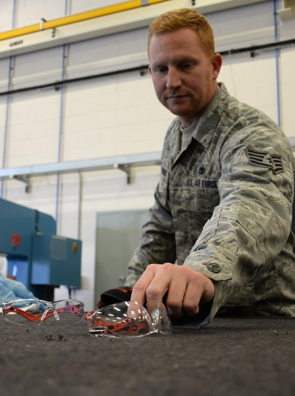 U.S. Air Force Staff Sgt. Zachary Sidlovsky, 100th Maintenance Squadron Aircraft Structural Maintenance craftsman, picks up safety glasses before carrying out his task Oct. 17, 2016, on RAF Mildenhall, England. Safety equipment is vital for maintainers as they carry out their duties. (U.S. Air Force photo by Gina Randall)