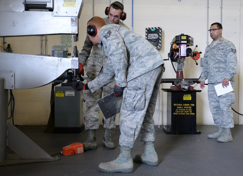 U.S. Air Force Staff Sgt. Jose Martinez, right, 100th Air Refueling Wing NCO in charge of inspections and analysis, observes U.S. Air Force Staff Sgt. Zachary Sidlovsky, front, 100th Maintenance Squadron Aircraft Structural Maintenance craftsman, and U.S. Air Force Airman 1st Class Devon Postlewait, 100th MXS ASM apprentice, while they modify a piece of sheet metal Oct. 17, 2016, on RAF Mildenhall, England. Before operating the machinery the Airmen put on the correct personal protective equipment. (U.S. Air Force photo by Gina Randall)