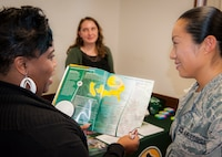Senior Airman Christina Faro, 96th Aerospace Medicine Squadron, receives information from Donna Shoebrook, Saint Leo University staff coordinator, at the Education Center open house Oct. 13 at Eglin Air Force Base, Fla.  Four universities and one college were presented to promote awareness of the opportunities to pursue higher education on the base.  (U.S. Air Force photo/Kevin Gaddie)