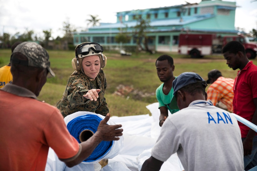 Marine Corps Gunnery Sgt. Brianna Conway, center, and Haitian volunteers unload supplies from a CH-53 Super Stallion helicopter at Les Cayes, Haiti, Oct. 17, 2016. Conway is assigned to the 24th Marine Expeditionary Unit. Marine Corps photo by Cpl. Brianna Gaudi
