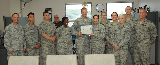 Senior Airman Maria Camunez, 22nd Aerospace Medical Squadron public health technician, poses with Col. Phil Heseltine, 22nd Air Refueling Wing vice commander, 22nd AMDS leadership and members of the 22nd AMDS public health section, Oct. 12, 2016, at McConnell Air Force Base, Kan. Camunez received the spotlight performer for the week of Sept. 26-30. (U.S. Air Force photo/Airman 1st Class Jenna K. Caldwell)