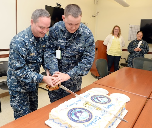 In commemoration of the U.S. Navy's 241st birthday, the most senior and junior Sailors in attendance, Navy Capt. Michael Service (left) and Seaman Kyle Jacobs (right), respectively, cut the traditional birthday cake. The ceremony was held in the conference room at Naval Branch Health Clinic-Albany at Marine Corps Logistics Base Albany, Oct. 14.