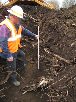 "Michael Shaffer, a civil engineer from the U.S. Army Corps of Engineers' Walla Walla District, measures the depth of root intrusion on the Mill Creek Levee Dec. 9, 2015, following Phase-1 maintenance removal of the land-side vegetation which jeopardized the structural integrity of the levee. District Geotechnical Section levee experts examined several test pits excavated at various points along the mile-long levee and determined removing problematic roots would require ""grubbing"" roughly two feet into the levee. In some locations, where tree roots have extended deeper into the levee structure, more extensive excavation and repairs may be required. Phase-2 repair work on the south levee from the division works beginning near the Mill Creek Office, progressing toward the Jones Ditch is slated to begin in early December 2016 and take approximately 3 months to complete. Additional Phase-2 repair work will occur as funding becomes available."