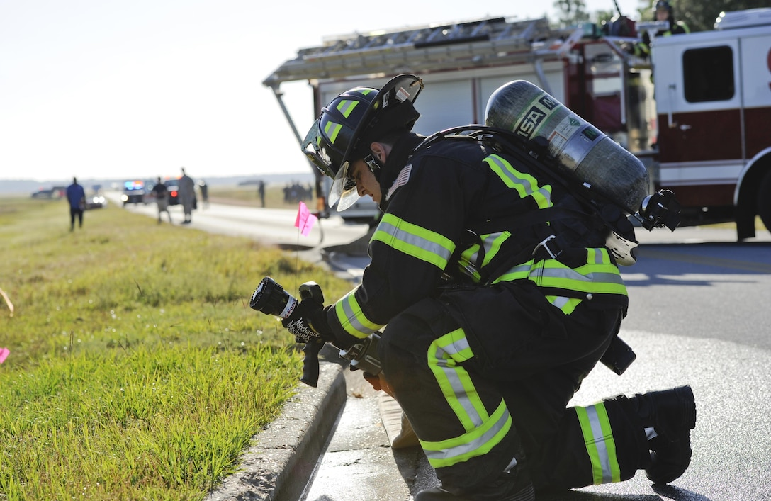 U.S. Air Force Senior Airman Cody Gadsbyhull, 325th Civil Engineer Squadron fire protection specialist, places a fire hose in a drainage ditch during a fuel spill exercise near the 325th Logistics Readiness Squadron fuel depot at Tyndall Air Force Base, Fla., Oct. 13, 2016. The purpose of the exercise was to train Airmen to respond to a simulated fuel spill in a safe and controlled environment. (U.S. Air Force photo by Senior Airman Solomon Cook/Released)