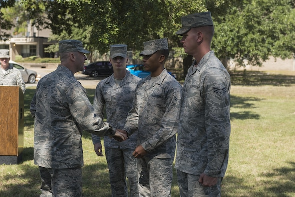 Col. Danny Davis, 81st Mission Support Group commander, presents Airman 1st Class Anthony Glisson, Air Force Honor Guard Mobile Training Team pallbearer instructor, with a unit coin after a mock active duty funeral and graduation ceremony Oct. 12, 2016, on Keesler Air Force Base, Miss. Keesler Honor Guard members were trained on the proper wear of the ceremonial uniform, firing party, presentation of the colors and pallbearer duties during an eight day course with the Air Force Honor Guard Mobile Training Team. The team ended the training with the mock funeral and graduation ceremony. (U.S. Air Force photo by Andre' Askew/Released)