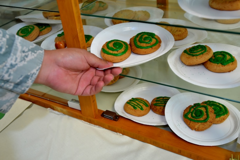A member of the 111th Attack Wing takes one of the green-iced cookies as part of the Wing's Green Dot program reminder event at Horsham Air Guard Station, Pa. Oct. 15, 2016. Green Dot is a program used to train all active duty, Reserve and National Guard Airmen in being effective bystanders by stepping in and stopping possible assaults. (U.S. Air National Guard photo by Tech. Sgt. Andria Allmond)