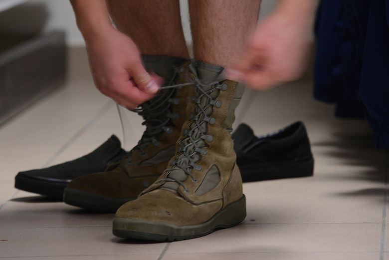 An Airman laces up a pair of boots during the Airman's Attic reopening at Aviano Air Base, Italy on Oct. 19, 2016. The Airman's Attic recently moved and changed their hours to accommodate Airmen. (U.S. Air Force photo by Staff Sgt. Andrew M. Satran/Released)