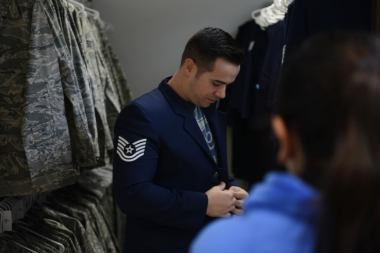 Staff Sgt. Eric Newell, 31st Maintenance Squadron aircraft fuels system repair technician, tries on a uniform item during the Airman's Attic reopening at Aviano Air Base, Italy on Oct. 19, 2016. The Airman's Attic supports military members E-5 and below and their family members with a variety of household goods and clothing items with the exception of uniform items which are available for all ranks. (U.S. Air Force photo by Staff Sgt. Andrew M. Satran/Released)