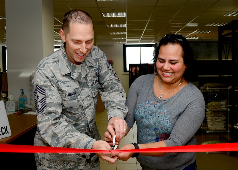 Command Chief Master Sgt. Matt Lusson, 31st Fighter Wing command chief and Lyly Granfield, Airman's Attic volunteer, cut the ribbon during the Airman's Attic reopening at Aviano Air Base, Italy, Oct. 17, 2016. During its two-week closure, volunteers remodeled, restocked and filtered through donations in order to provide the best products to customers. (U.S. Air Force photo by Senior Airman Areca T. Bell/Released)