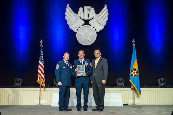 Master Sgt. Stuart Wilson poses with Chief Master Sgt. Brendan Criswell, Air Force Space Command Command Chief and Mr. Scott Van Cleef, Chairman, Air Force Association. Sgt. Wilson, Operations Superintendent, 92nd Cyberspace Operations Squadron, Joint Base San Antonio-Lackland, Texas, received the award for the C4 professional who most enhanced the United States Air Force's warfighting capability. The 92nd COS is aligned under the 688th Cyberspace Wing, 24th Air Force, Air Force Space Command.
