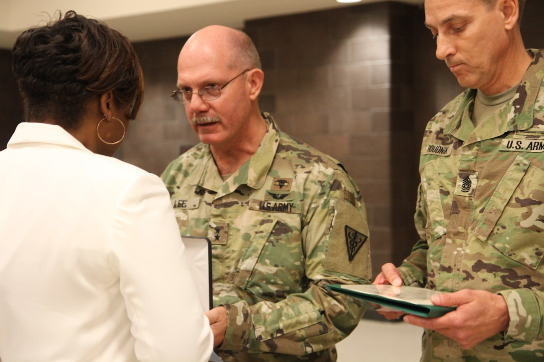 Maj. Gen. William Lee and Command Sgt. Maj. Robert Boudnik present an award to Mrs. Graham in honor of Master Sgt. Steven Graham during the memorial ceremony, Oct. 15, 2016.  Photo captured by Maj. Satomi Mack-Martin.