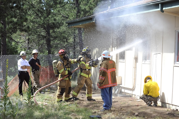 Firefighters from the 10th Civil Engineer Squadron Fire Department douse a structure during a fire-response exercise at the U.S. Air Force Academy. Academy firefighters will compete in the Firefighter Would Championship beginning Oct. 24, 2016 in Montgomery, Alabama. (U.S. Air Force photo/Jason Gutierrez)