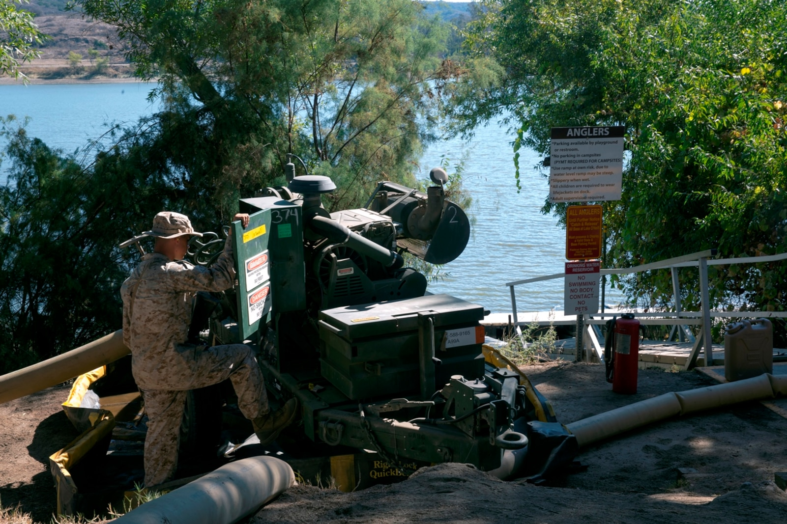 U.S. Marine Corps Pfc. Silas Thomas, from Colebrook, Ohio, a bulk fuel specialist with Bulk Fuel Company, 7th Engineer Support Battalion, inspects one of the 600-gallon-per-minute pumps while it draws water from Lake O'Neill to take to the 200,000 gallon storage site during the bulk fuel Marine Corps Combat Readiness Evaluation on Camp Pendleton, Calif., Oct. 12, 2016. By using water from Lake O'Neill, the Marines were able to simulate the process of pumping fuel from ship to shore in an expeditionary environment.