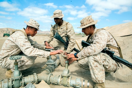 U.S. Marine Corps Cpl. Samuel Ruizlopez, from Aberdeen, Washington, a bulk fuel specialist with Bulk Fuel Company, 7th Engineer Support Battalion, instructs Pfc. Jonathan Arevalo, from Brooklyn, New York, and Pfc. Carlos Effiogalvez, from New York City, how to turn valves to control water flow into a 50,000 gallon bag during the bulk fuel Marine Corps Combat Readiness Evaluation on Camp Pendleton, Calif., Oct. 12, 2016. By using water from Lake O'Neill, the Marines were able to simulate the process of pumping fuel from ship to shore in an expeditionary environment.