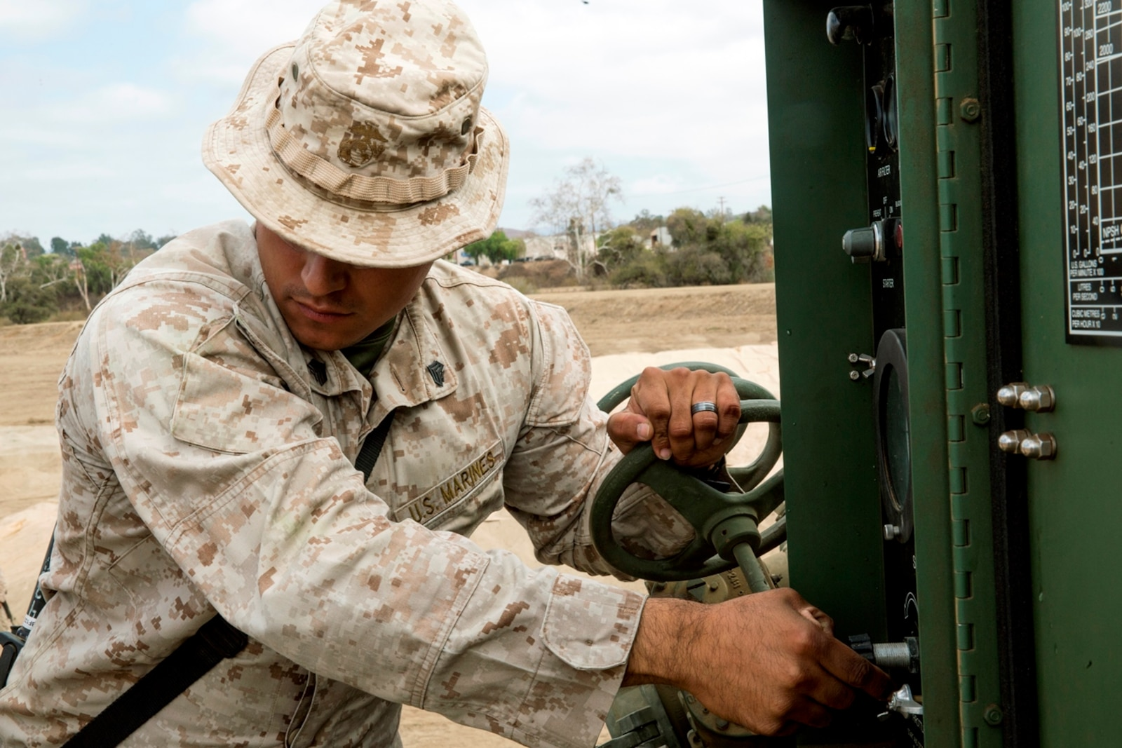 U.S. Marine Corps Sgt. Oscar Tapia, from Salinas, Calif., a bulk fuel specialist with Bulk Fuel Company, 7th Engineer Support Battalion, controls the water pressure of a 600-gallon-per-minute pump while it flows through a 6-inch hose reel system into one of the 50,000 gallon bags at the storage site during the bulk fuel Marine Corps Combat Readiness Evaluation on Camp Pendleton, Calif., Oct. 12, 2016. There are three 200,000 gallon storage sites totaling 600,000 gallons in the MCCRE as well as two 120,000 gallon sites.