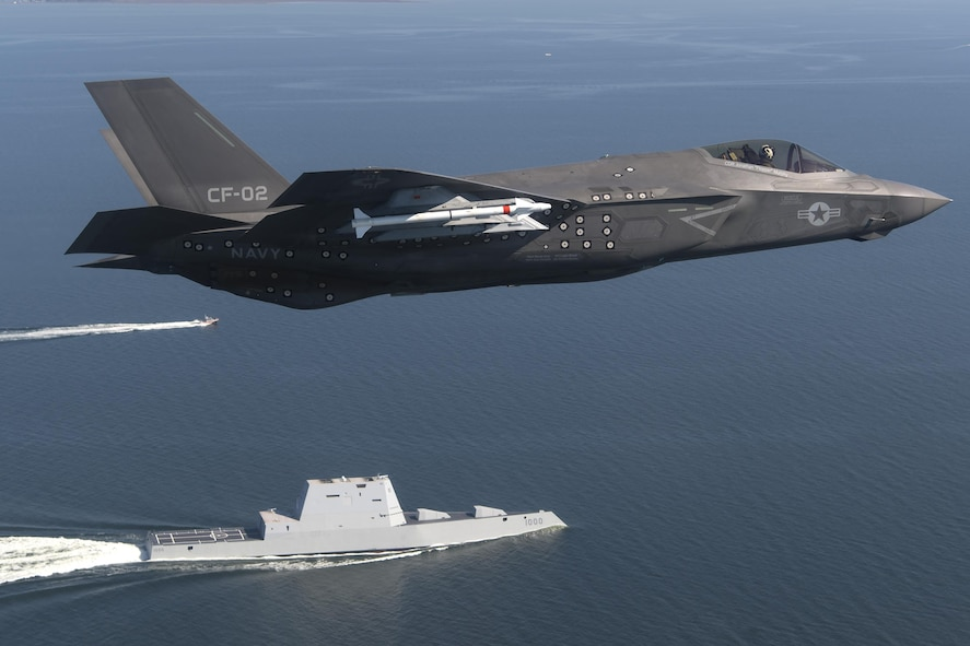 An F-35 Lightning II flies over the USS Zumwalt in the Chesapeake Bay.