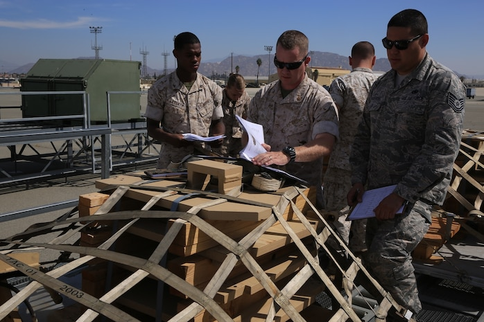 U.S. Marine Corps Lance Cpl. Bryson Leysath, Chief Warrant Officer 2 Robert Hallett and U.S. Air Force Tech. Sgt. Geoffrey Gaeraths inspect pallets containing M-88A2 HERCULES equipment at March Air Force Reserve Base, Calif., Oct. 13, 2016. Leysath, from Augusta, Ga., is an embarkation specialist with Combat Logistics Regiment 15, Hallett, from Mesa, Az., is a mobility officer with CLR 15 and Gaeraths, from Victorville, Calif., is a joint inspector with 452nd Logistics Readiness Squadron.