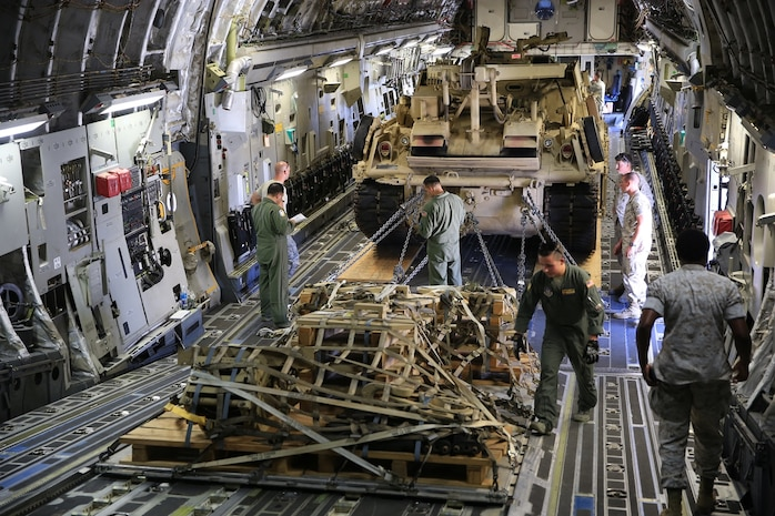 U.S. Marines and Airmen work together to properly secure the M-88A2 HERCULES and pallets in the C-17 Globemaster III at March Air Force Reserves Base, Calif., Oct. 14, 2016. Marines and Airmen checked all chains and pallets before flying to Marine Corps Air Ground Combat Center Twentynine Palms, Calif.