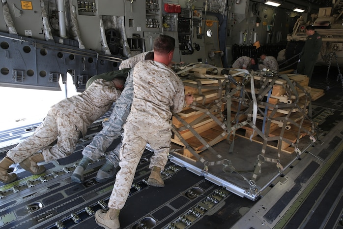 U.S. Marines and Airmen work hand-in-hand to load a pallet, filled with an M-88A2 HERCULES' armored side skirts and front winch aboard the C-17 Globemaster III at March Air Force Reserves Base, Calif., Oct. 14, 2016. The C-17 flew to Marine Corps Air Ground Combat Center Twentynine Palms, Calif., to deliver the M-88A2 recovery vehicle for use by Combat Logistics Company 13.