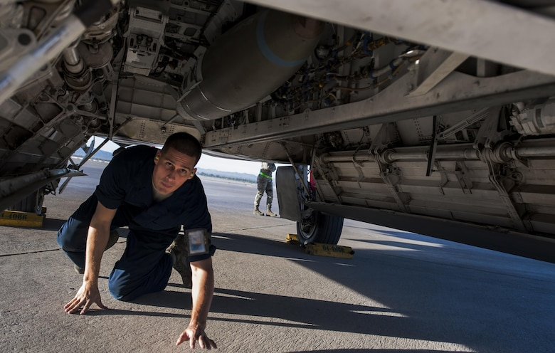 An Airman assigned to the Raptor Aircraft Maintenance Unit checks a loaded munition on an F-22 Raptor during the 57th Wing's third quarter weapons load crew competition at Nellis Air Force Base, Nev., Oct. 7. The quarterly competition highlights Airmen for their loading skill and duty performance.(U.S. Air Force photo by Airman 1st Class Kevin Tanenbaum/Released)