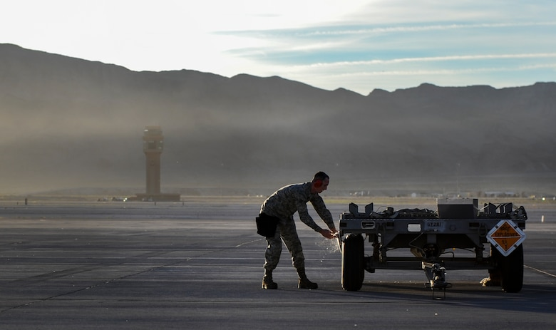 An Airman from the 757th Aircraft Maintenance Squadron secures a weapons cart during the 57th Wing's third quarter weapons load crew competition at Nellis Air Force Base, Nev., Oct. 7. During the competition, load crew members are evaluated on a written test, dress and appearance inspection, composite tool kit  inspection, and the weapons load. (U.S. Air Force photo by Airman 1st Class Kevin Tanenbaum/Released)