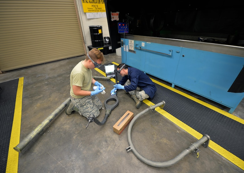 Airman 1st Class Brian Sheldon, a non-destructive inspection journeyman with the 1st Special Operations Maintenance Squadron, stands with a magnetic particle unit at Hurlburt Field Fla., Oct. 17, 2016. A magnetic particle unit blocks light from hitting the prop rod allowing the florescent light to glow indicating imperfections on parts. These specialist use noninvasive methods to inspect the insides of metal objects to identify possible defects in systems and equipment. (U.S. Air Force photo by Senior Airman Andrea Posey)