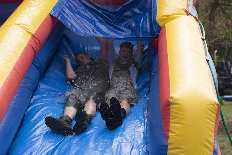 """Senior Airman Travis Hahn-Holmes, 85th Engineering Installation Squadron cable and antenna maintainer, and Staff Sgt. Brendon Wright, 85th EIS airfield systems project manager, participate in the running of the """"Grog"""" obstacle course during the 85th EIS Combat Dining-In at the 85th EIS compound Oct 7, 2016, on Keesler Air Force Base, Miss. The combat dining-in is a military tradition which promotes good fellowship and esprit de corps throughout the unit. (U.S. Air Force photo by Andre' Askew/Released)"""