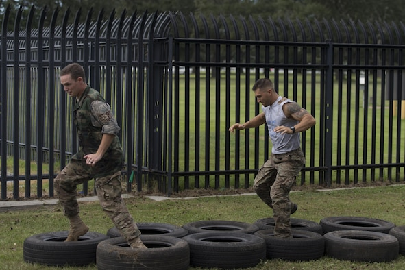 Tech. Sgt. Jamie Felkins and Staff Sgt. Tyler Crawford, 85th Engineering Installation Squadron cable and antenna maintainers, negotiate a tire obstacle course during the 85th EIS Combat Dining In at the 85th EIS compound Oct 7, 2016, on Keesler Air Force Base, Miss. The combat dining-in is a military tradition which promotes good fellowship and esprit de corps throughout the unit. (U.S. Air Force photo by Andre' Askew/Released)