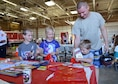 Staff Sgt. Kessler Hamon, 310th Aircraft Maintenance Unit crew chief, helps his kids pick out fire prevention material during the 56th Civil Engineer Squadron fire station open house, Oct. 15, 2016 at Luke Air Force Base, Ariz. The fire station open house was available to the public and featured free food, displays, demonstrations and games for children.(U.S. Air Force photo by Senior Airman Devante Williams)