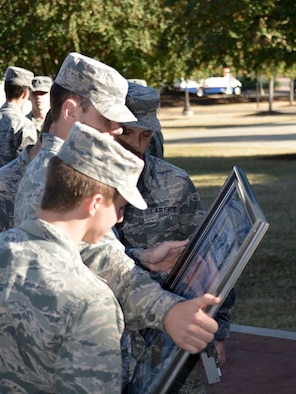 Three Air Force ROTC cadets from Auburn University's Detachment 005 look at artwork following a career day Oct. 13th at Auburn University. The Gathering of Eagles Foundation presented the ROTC detachment with the framed lithograph, featuring men and women who made lasting contributions to air power, to inspire the cadets as they prepare for a career in the Air Force.  (US Air Force photo by Maj. Will Powell)