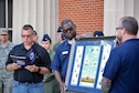 Maj. Stan Grodrian, left, Gathering of Eagles Foundation president and ACSC student, reads a citation during a gift presentation Oct. 13th at Auburn University.  Students and faculty from ACSC traveled to Auburn University's AFROTC detachment to participate in the detachment's career day.  After talking with cadets about career opportunities in the Air Force, the Gathering of Eagles Foundation presented the detachment with a lithograph of previous Eagles who made lasting contributions to air power.  (US Air Force photo by Maj. Will Powell)